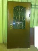 Стальная дверь с коваными завитками и большим тонированным стеклопакетом